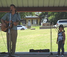 Paul is joined on stage by a young fan while performing at the Children's Festival at the 2008 Woody Guthrie Folk Festival - July 12, 2008.