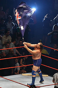 Duggan waving an Australian flag during his ring entrance in Australia, 2007, with his 2x4 in the corner