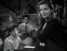 Bacall in her first movie, To Have and Have Not; Hoagy Carmichael is in the background playing the piano