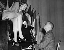 Bacall sits atop the piano while Vice President Harry S Truman plays the piano at the National Press Club Canteen. (February 10, 1945)
