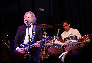 Mickey Hart (in background, playing drums) and Bob Weir (playing guitar) performing at the Mid-Atlantic Inaugural Ball during the presidential inauguration of Barack Obama, January 20, 2009.