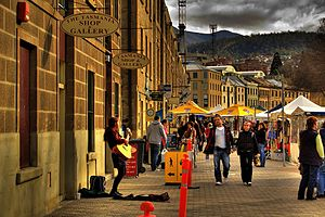 "Salamanca Place, Hobart (2007). In mid-1974 Kelly made his first public performance in a folk club along this street, ""[It] was a row of warehouses gradually being converted into galleries, shops and cafés. The club was upstairs above a jewellery and craft store. Tables and chairs on a wooden floor with a small stage ... By the time I got onstage I was shaking. I sang Bob Dylan's 'Girl from the North Country', the Nashville Skyline version, and 'The Streets of Forbes', a folk song about the bushranger Ben Hall. Somehow I got through my two-song gig, headed straight for the bar for more beer..."" – Kelly (2010), How to Make Gravy, pages 16–18.[29]"