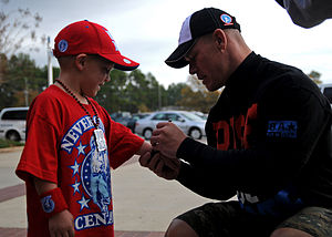 Cena signing merchandise for a young fan