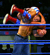 "Cena performing an ""FU"" (standing fireman's carry takeover) on Kurt Angle in January 2005."