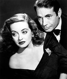 Davis posing as Margo Channing in a promotional image for All About Eve (1950). She is pictured with Gary Merrill, to whom she was married from 1950 to 1960 (her fourth and final husband)